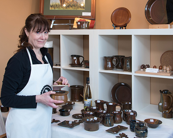 Rosemary, showing off some of her designs in her studio